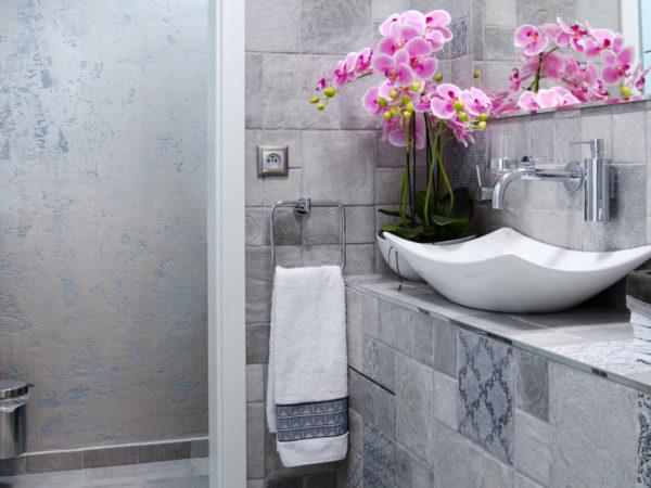 design interiéru koupelny s použitím antické zeminy, stříbrnomodrých obkladů a designových umyvadel.